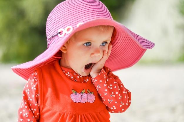 Bambina bionda con cappello sulla spiaggia in un vestito rosso in primavera
