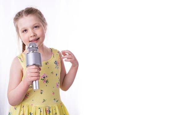 Una bambina bionda canta una canzone in un microfono nelle sue mani