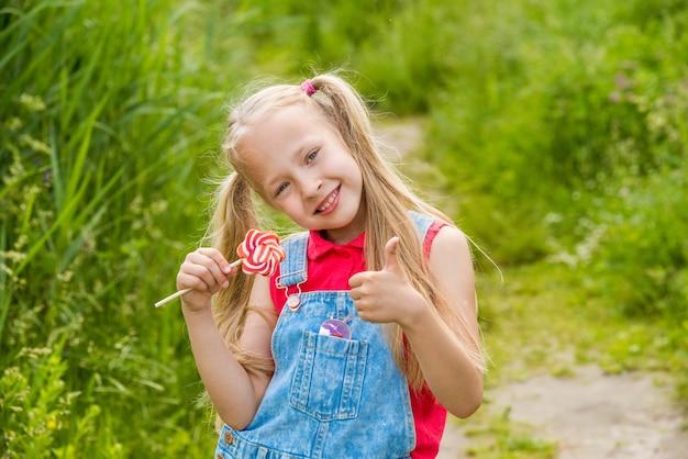 Bambina bionda con i capelli lunghi e caramelle su un bastone in mano