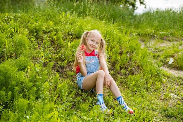 Bambina bionda con capelli lunghi e caramelle su un bastone