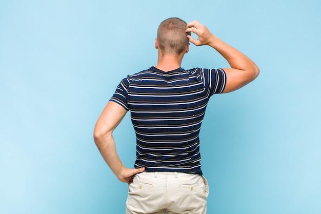 Uomo biondo che si sente incapace e confuso, pensando a una soluzione, con una mano sull'anca e l'altra sulla testa, vista posteriore