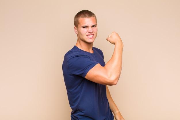 Uomo biondo che si sente felice, soddisfatto e potente, che flette in forma e bicipiti muscolosi, sembra forte dopo la palestra