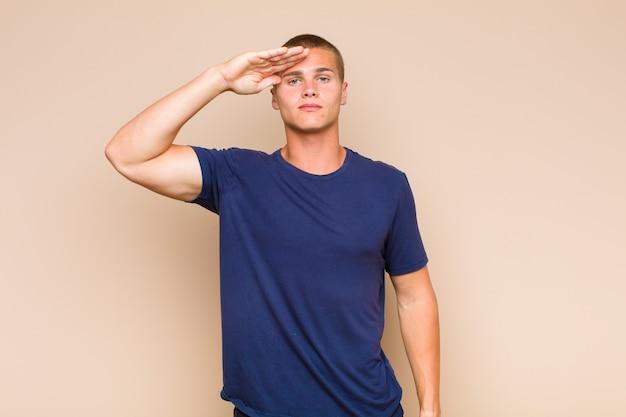 Uomo biondo che saluta con un saluto militare in un atto di onore e patriottismo, mostrando rispetto