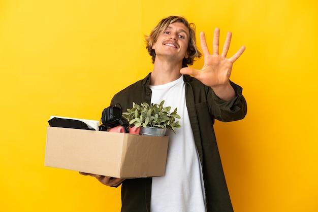 Uomo biondo che fa una mossa mentre prende in mano una scatola piena di cose isolate
