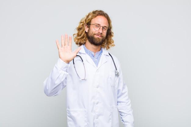 Uomo biondo che sorride allegramente e allegramente, agitando la mano, dandoti il benvenuto e salutandoti o salutandoti