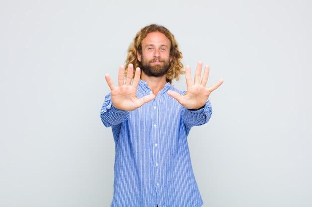 Uomo biondo che sorride e sembra amichevole, mostrando il numero dieci o decimo con la mano in avanti, conto alla rovescia