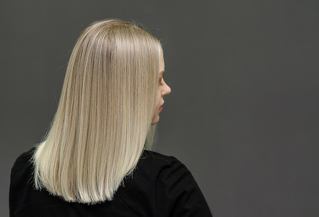 Modello biondo con capelli lisci, guarda da dietro. risultato decolorante dei capelli. spazio per il testo