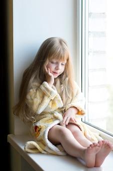 Una ragazza bionda di nove anni con un accappatoio leggero è seduta sul davanzale della finestra vicino alla finestra triste