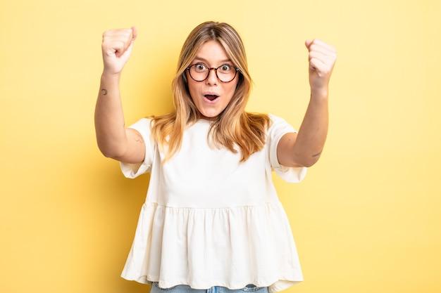 Bella donna bionda che celebra un incredibile successo come una vincitrice, sembra eccitata e felice dicendo: prendilo!