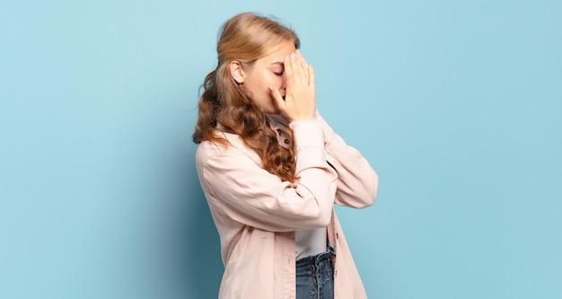 Donna graziosa bionda che copre gli occhi con le mani con uno sguardo triste e frustrato di disperazione, pianto, vista laterale