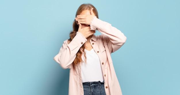 Donna graziosa bionda che copre il viso con entrambe le mani dicendo no alla telecamera! rifiutare le immagini o vietare le foto