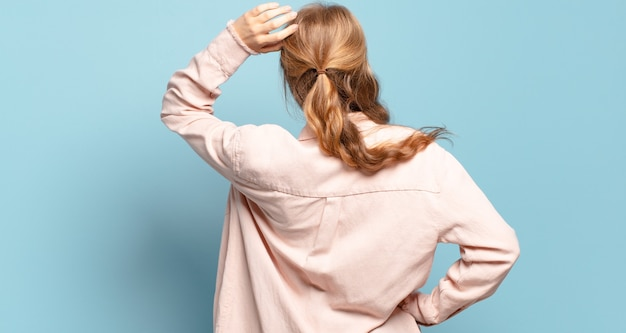 Donna graziosa bionda che si sente incapace e confusa, pensando a una soluzione, con una mano sull'anca e l'altra sulla testa, vista posteriore