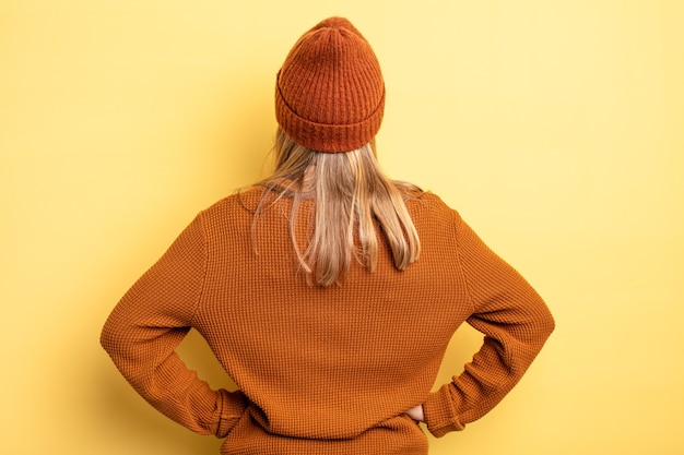 Bella donna bionda che si sente confusa o piena o dubbi e domande, chiedendosi, con le mani sui fianchi, vista posteriore