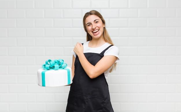Bella donna bionda che si sente felice, positiva e di successo, motivata quando affronta una sfida o celebra buoni risultati