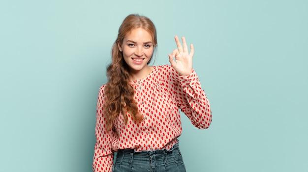 Donna graziosa bionda che si sente felice, rilassata e soddisfatta, mostrando l'approvazione con il gesto giusto, sorridente