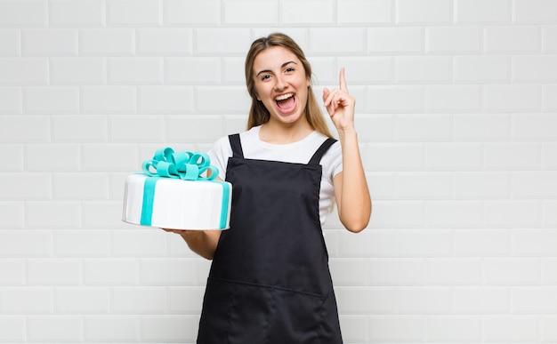 Bella donna bionda che si sente come un genio felice ed eccitato dopo aver realizzato un'idea, alzando allegramente il dito, eureka!