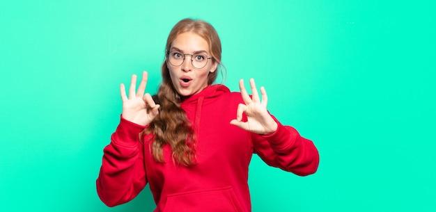 Donna graziosa bionda che si sente scioccata, stupita e sorpresa, mostrando approvazione facendo segno ok con entrambe le mani