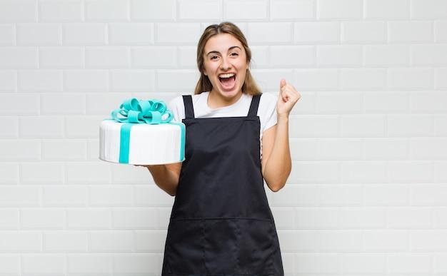Bella donna bionda che si sente scioccata, eccitata e felice, ride e celebra il successo, dicendo wow!