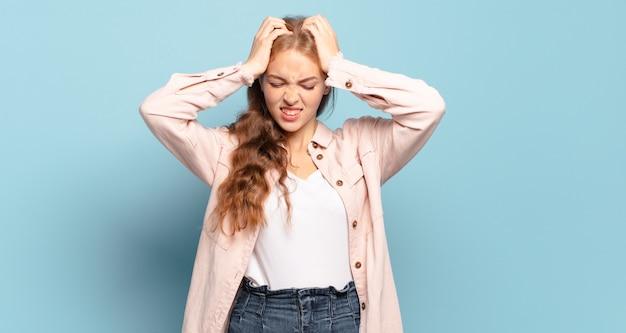 Bella donna bionda che si sente stressata e frustrata, alza le mani sulla testa, si sente stanca, infelice e con emicrania