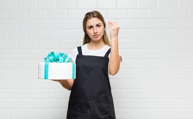 Bella donna bionda che fa un gesto di capice o denaro, dicendoti di pagare i tuoi debiti!