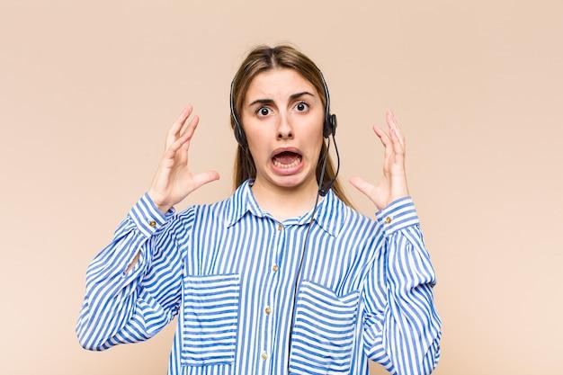 Bella donna bionda che grida con le mani in aria, sentendosi furiosa, frustrata, stressata e sconvolta