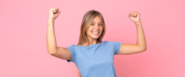 Bella donna bionda che grida trionfalmente, sembra un vincitore eccitato, felice e sorpreso, festeggiando