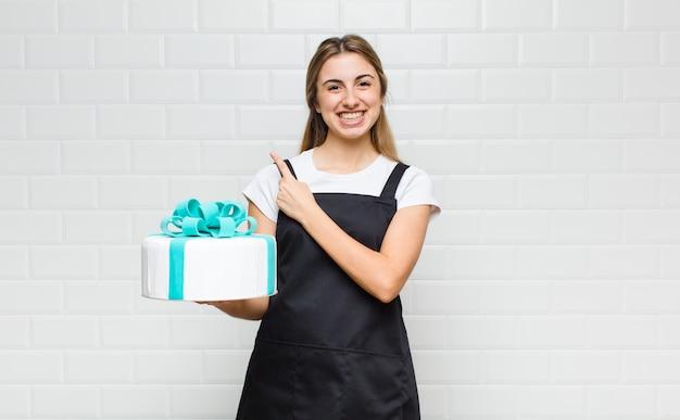 Donna graziosa bionda che sorride allegramente, sentendosi felice e indicando il lato e verso l'alto, mostrando l'oggetto nello spazio della copia