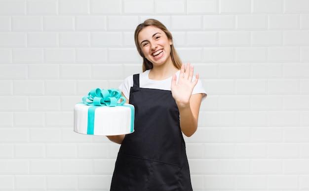 Bella donna bionda che sorride allegramente e allegramente, agitando la mano, dandoti il benvenuto e salutandoti o salutandoti