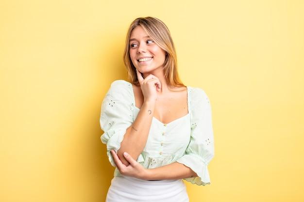 Bella donna bionda che sorride con un'espressione felice e sicura con la mano sul mento, chiedendosi e guardando di lato