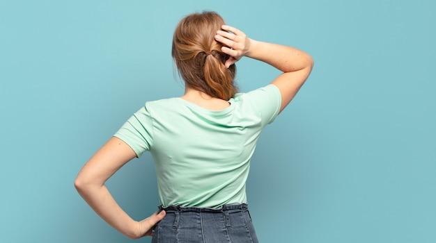 Bella donna bionda pensando o dubitando, grattandosi la testa, sentendosi perplessa e confusa, vista posteriore o posteriore