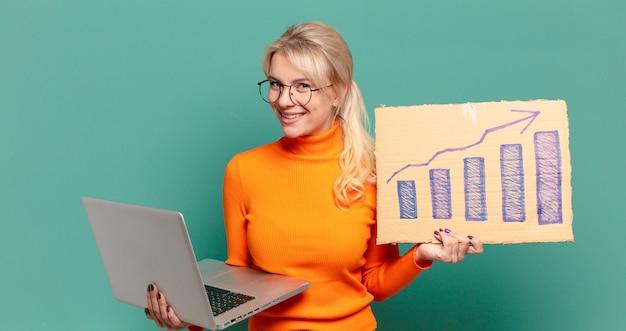 Donna graziosa bionda con un grafico a barre in aumento e un computer portatile