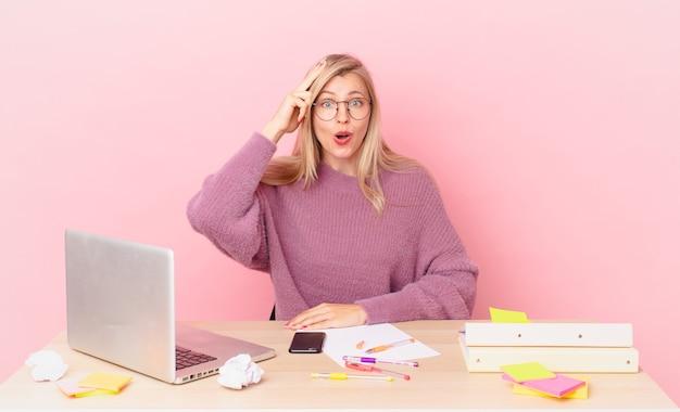 Donna bionda graziosa giovane donna bionda che sembra felice, stupita e sorpresa e lavora con un laptop
