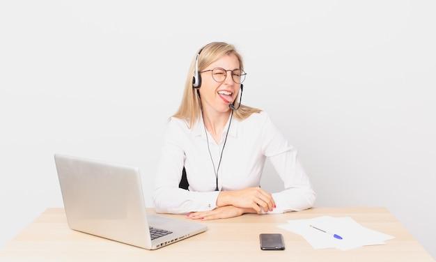 Bionda bella donna giovane donna bionda con un atteggiamento allegro e ribelle, scherzando e tirando fuori la lingua e lavorando con un laptop