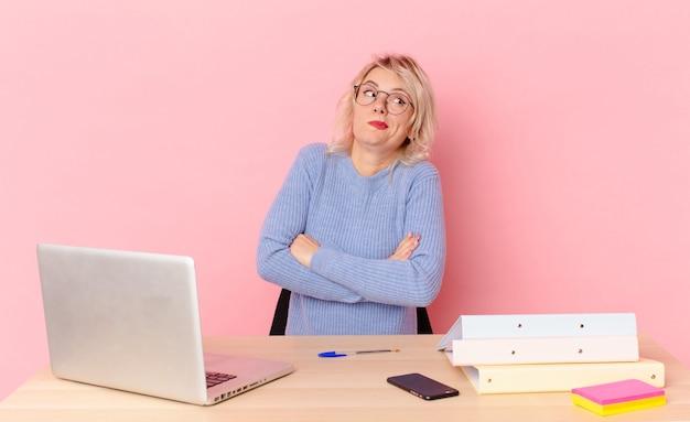 Donna graziosa bionda giovane donna graziosa che alza le spalle, sentendosi confusa e incerta. concetto di scrivania dell'area di lavoro