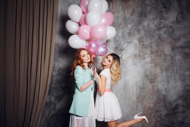 Bionda e rossa. due giovani donne affascinanti alla festa. donna felice e allegra con palloncini.