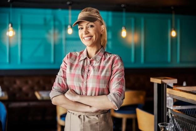 La cameriera bionda indossa una camicia a quadri, un berretto e un grembiule. ha le braccia incrociate e guarda dritto davanti con un sorriso