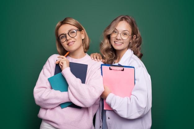 Sorelle bionde con gli occhiali sorridenti e in posa su una parete verde dello studio