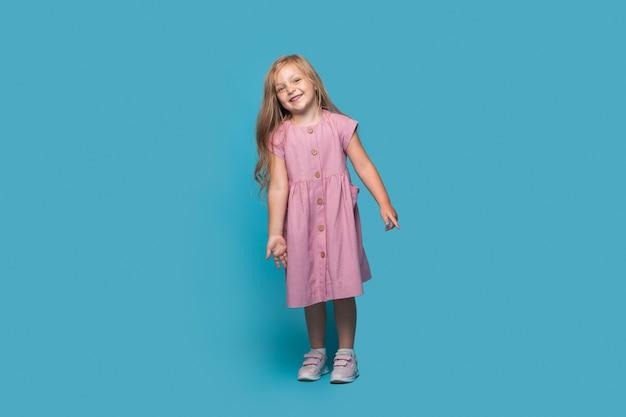 Piccola ragazza bionda che indossa un abito rosa sorride alla telecamera mentre posa su una parete blu dello studio
