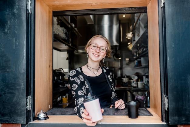 Una cameriera bionda sorridente sta servendo caffè da asporto attraverso la finestra.