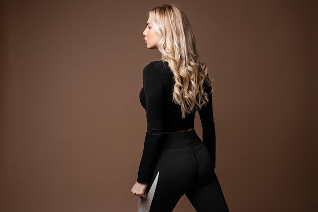 Ragazza sportiva bionda in abbigliamento sportivo nero in posa in studio. foto di una ragazza con un corpo perfetto su sfondo beige. forza e motivazione