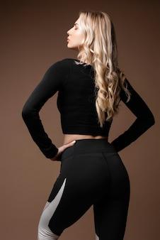 Donna sportiva bionda con corpo abbronzato sottile in abiti sportivi neri in posa su sfondo beige. retrovisore