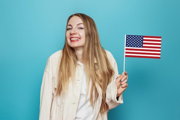 Studentessa bionda tiene una piccola bandiera americana e sorride