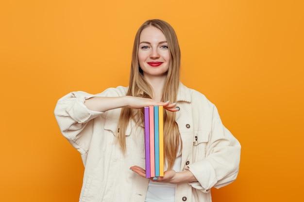 Ragazza studentessa bionda che mostra un sacco di libri isolato su sfondo arancione studio