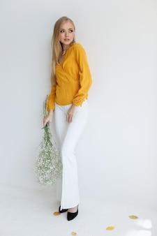 Bionda in un'immagine alla moda alla moda con i fiori asciutti alla parete bianca. stilista autunnale