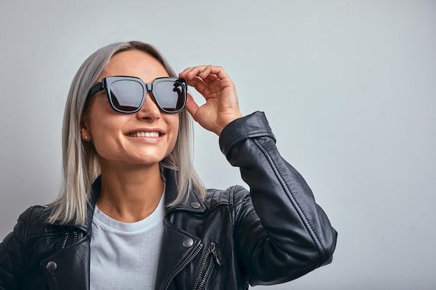 Giacca di pelle bionda occhiali da sole su un muro grigio. copia spazio