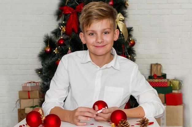 Ragazzo adolescente biondo vestito con una camicia bianca che scrive una lettera a babbo natale a casa