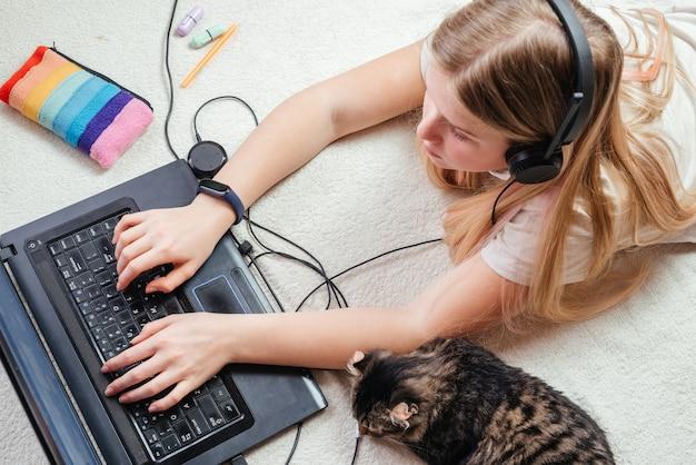 Una ragazza adolescente bionda in cuffie sdraiato sul letto con il suo gatto domestico e utilizzando il suo computer portatile