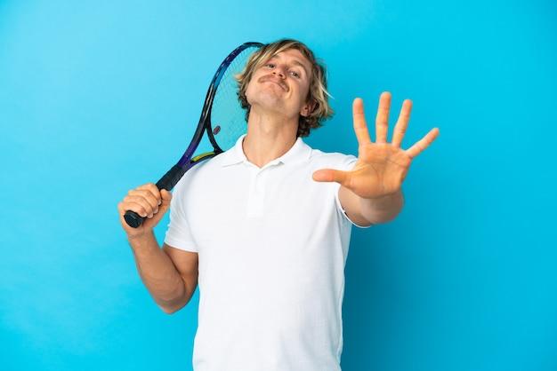 Uomo biondo del giocatore di tennis isolato sulla parete blu che conta cinque con le dita