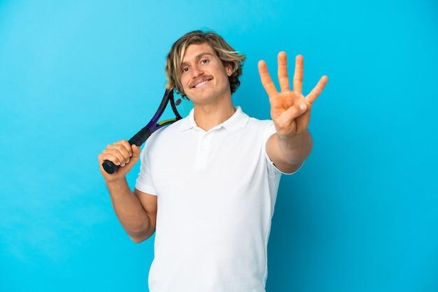 Uomo biondo del giocatore di tennis isolato sulla parete blu felice e contando quattro con le dita