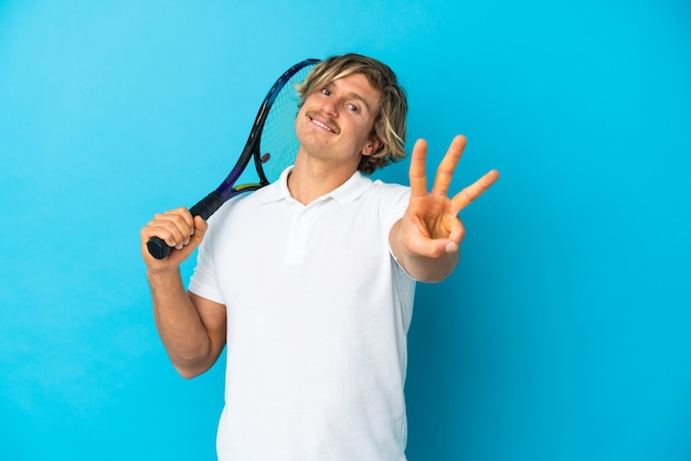 Uomo biondo del giocatore di tennis isolato sulla parete blu felice e contando tre con le dita